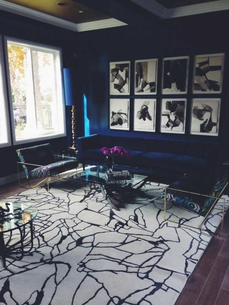 70s-inspired interior photo with navy velvet sofa, navy walls, abstract black and white rug