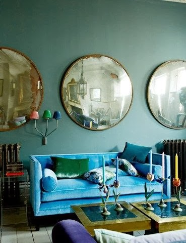 Bright blue sofa with a green cushion in a muted teal painted room